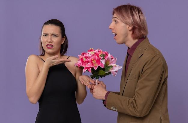 Onder de indruk van een jonge knappe man die een boeket bloemen vasthoudt en naar een onwetende mooie jonge vrouw kijkt