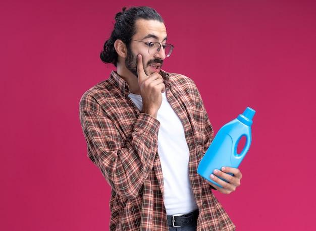 Onder de indruk van een jonge knappe schoonmaakster die een t-shirt draagt en kijkt naar een schoonmaakmiddel dat de vinger op de wang legt die op een roze muur is geïsoleerd