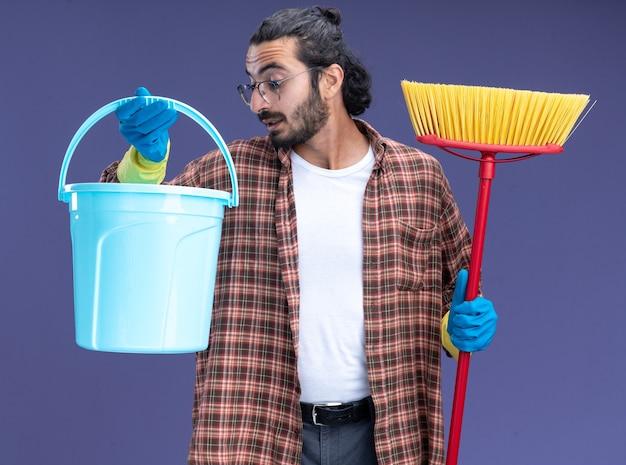Onder de indruk van een jonge knappe schoonmaakster met een t-shirt en handschoenen die een dweil vasthoudt en naar een emmer in zijn hand kijkt, geïsoleerd op een blauwe muur