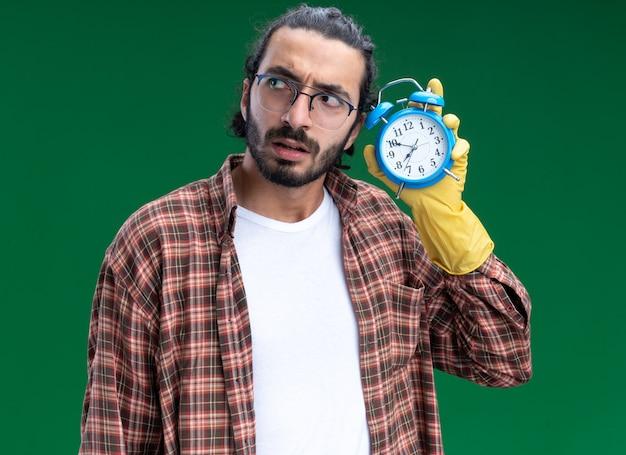 Onder de indruk van een jonge knappe schoonmaakster met een t-shirt en handschoenen die een wekker vasthoudt en luistert die op een groene muur is geïsoleerd