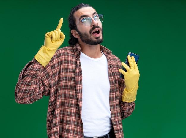 Onder de indruk van een jonge knappe schoonmaakster met een t-shirt en handschoenen met telefoonpunten op geïsoleerd op een groene muur