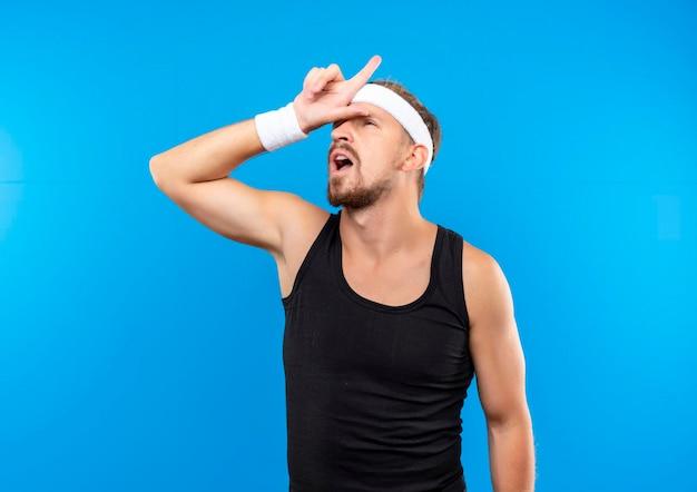Onder de indruk van een jonge knappe sportieve man met een hoofdband en polsbandjes die de hand op het voorhoofd legt en omhoog wijst, geïsoleerd op een blauwe muur