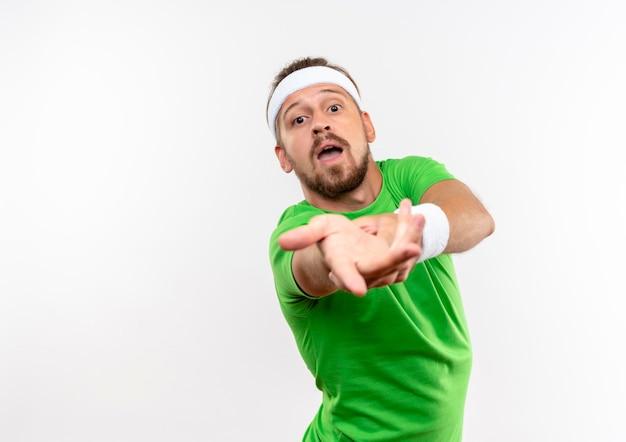 Onder de indruk van een jonge knappe sportieve man met een hoofdband en polsbandjes die de hand uitstrekken, geïsoleerd op een witte muur met kopieerruimte