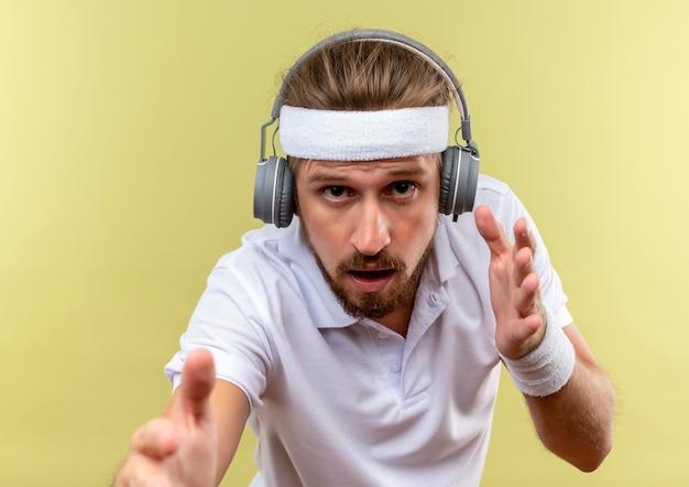 Onder de indruk van een jonge knappe sportieve man met een hoofdband en polsbandjes en een koptelefoon die zijn handen uitstrekt en geïsoleerd op een groene muur