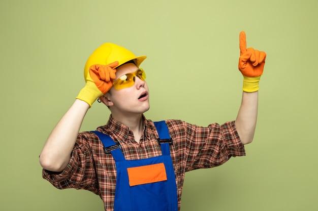 Onder de indruk van een jonge mannelijke bouwer die uniform en handschoenen met een bril draagt