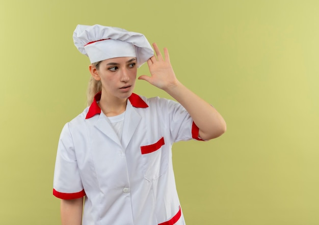 Onder de indruk van een jonge, mooie kok in uniform van de chef-kok die naar de zijkant kijkt en de hand in de buurt van het hoofd houdt en naar de zijkant kijkt die op een groene muur met kopieerruimte wordt geïsoleerd