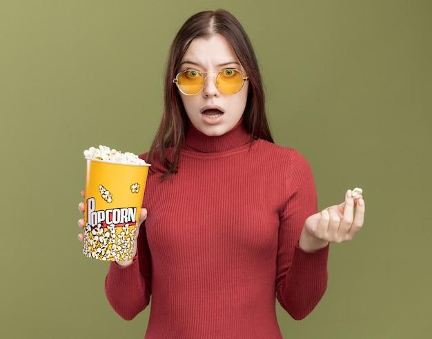 Onder de indruk van een jonge mooie vrouw die een zonnebril draagt met een emmer popcorn en een stuk popcorn en kijkt naar de voorkant geïsoleerd op een olijfgroene muur