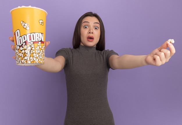 Onder de indruk van een jonge mooie vrouw die naar voren kijkt en een emmer popcorn en een stuk popcorn naar voren uitrekt, geïsoleerd op een paarse muur