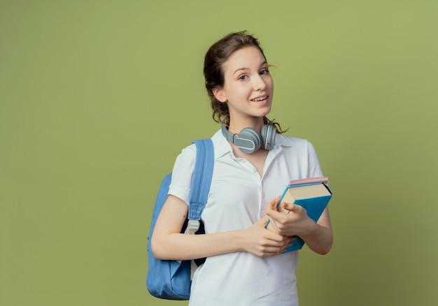 Onder de indruk van een jonge, mooie vrouwelijke student met een rugzak en een koptelefoon op de nek met een boek en een notitieblok