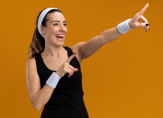 Onder de indruk van een jonge, vrij sportieve vrouw met een hoofdband en polsbandjes die naar de zijkant kijken en je gebaar maken dat op een oranje muur is geïsoleerd