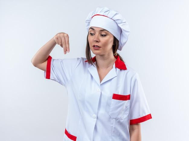 Onder de indruk van een jonge vrouwelijke kok die een uniform van een chef-kok draagt en doet alsof hij iets vasthoudt dat op een witte muur is geïsoleerd