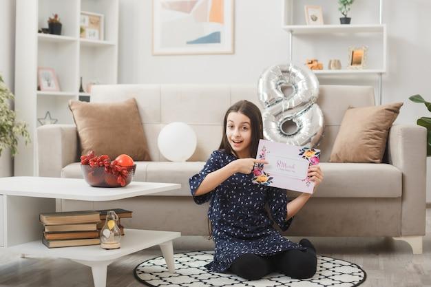 Onder de indruk van een klein meisje op een gelukkige vrouwendag zittend op de vloer en wijst naar een ansichtkaart in de woonkamer