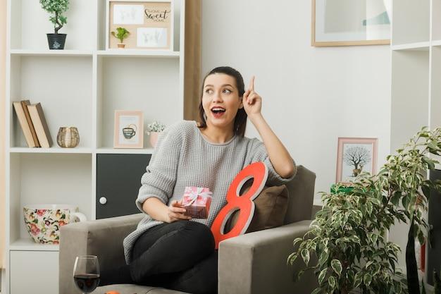 Onder de indruk van een mooi meisje op een gelukkige vrouwendag met een cadeautje zittend op een fauteuil in de woonkamer