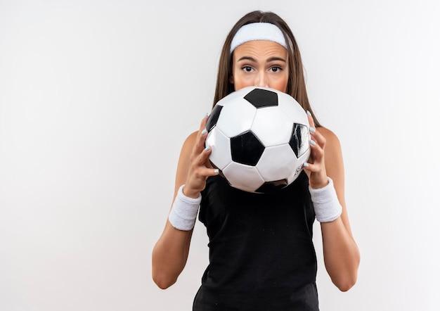Onder de indruk van een mooi sportief meisje met een hoofdband en een polsband die een voetbal vasthoudt en zich erachter verbergt, geïsoleerd op een witte muur met kopieerruimte
