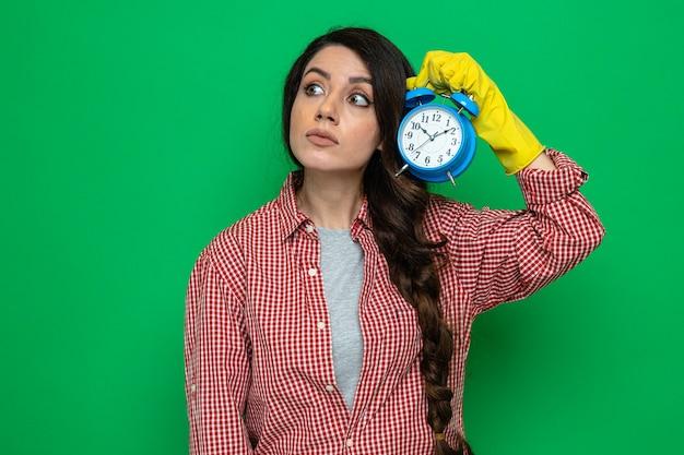 Onder de indruk van een mooie blanke schonere vrouw met rubberen handschoenen die een wekker vasthoudt en naar de zijkant kijkt