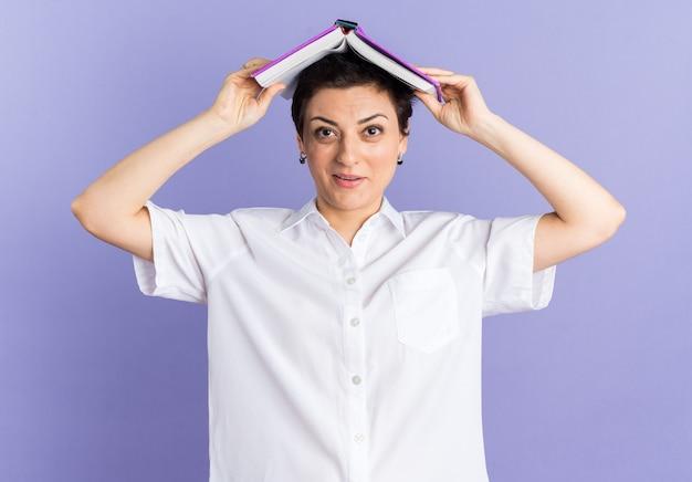 Onder de indruk van een vrouw van middelbare leeftijd die een open boek op het hoofd houdt en naar de camera kijkt