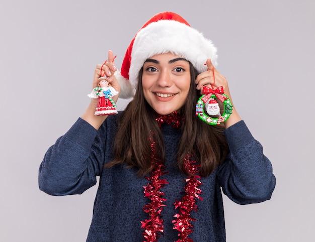 Onder de indruk van het jonge blanke meisje met kerstmuts en slinger om de nek houdt kerstboomspeelgoed geïsoleerd op een witte muur met kopieerruimte