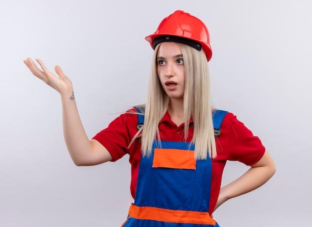 Onder de indruk van het jonge blonde meisje van de ingenieursbouwer in uniform die lege hand met een andere op taille toont die naar linkerkant op geïsoleerde witte ruimte kijkt