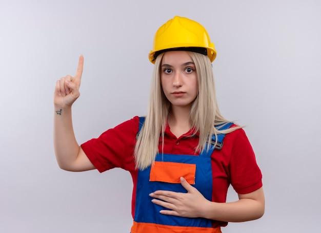 Onder de indruk van het jonge blonde meisje van de ingenieursbouwer in uniform die met hand op buik op geïsoleerde witte ruimte benadrukt