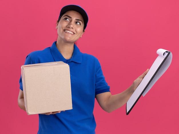 Onder de indruk van het kijken naar de zijkant van het jonge bezorgmeisje dat uniform draagt met de doos van de dopholding met klembord dat op roze muur wordt geïsoleerd