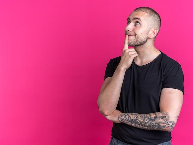 Onder de indruk van het opzoeken van een jonge knappe kerel met een zwart t-shirt die de vinger op de kin legt, geïsoleerd op een roze achtergrond met kopieerruimte