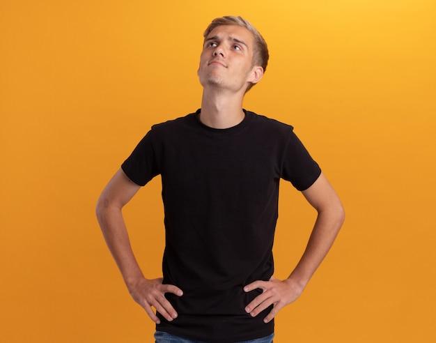 Onder de indruk van het opzoeken van een jonge knappe man met een zwart shirt die de handen op de heup legt, geïsoleerd op een gele muur