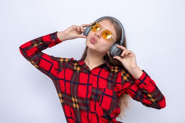 Onder de indruk van het opzoeken van een mooi klein meisje met een rood shirt en een bril met koptelefoon