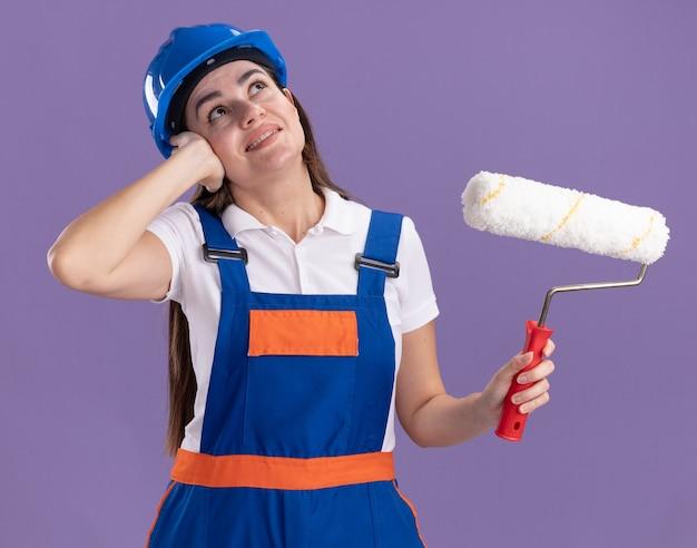 Onder de indruk van het opzoeken van jonge bouwersvrouw in uniforme holdingsrolborstel die hand op oor zet dat op purpere muur wordt geïsoleerd