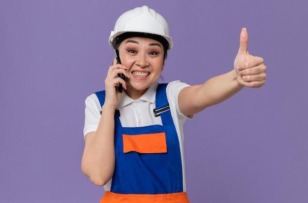 Onder de indruk van jong aziatisch bouwersmeisje met witte veiligheidshelm die aan de telefoon praat en omhoog duimt