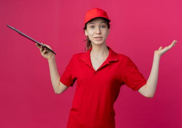Onder de indruk van jong, mooi bezorgmeisje in rood uniform en pet met klembord en lege hand op karmozijnrode ruimte