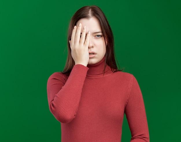 Onder de indruk van jong mooi meisje dat de helft van het gezicht bedekt met de hand geïsoleerd op een groene muur met kopieerruimte