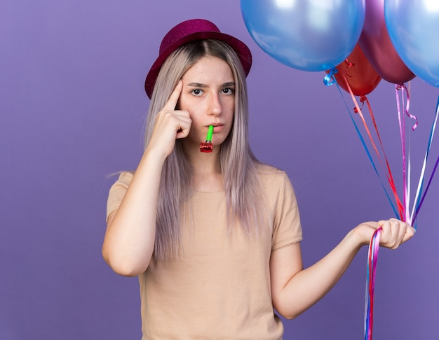 Onder de indruk van jong mooi meisje met feestmuts met ballonnen die feestfluitje blazen en vinger op tempel zetten die op blauwe muur is geïsoleerd