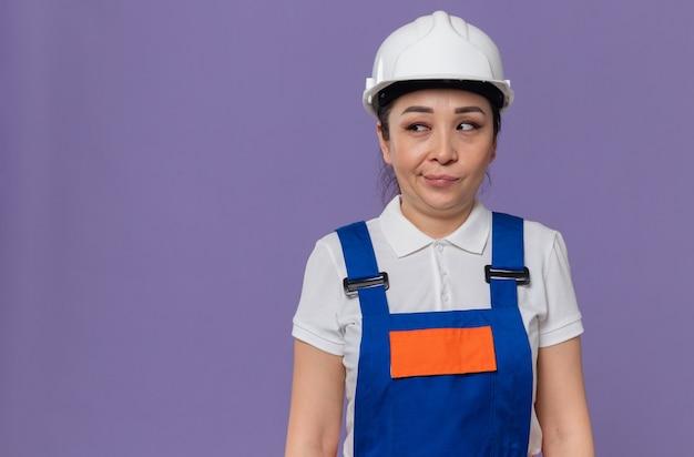 Onder de indruk van jonge aziatische bouwvrouw met witte veiligheidshelm die naar de zijkant kijkt