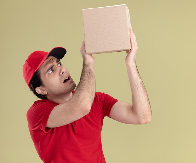 Onder de indruk van jonge bezorger in rood uniform en pet die opstaat en naar een kartonnen doos kijkt die op een olijfgroene muur is geïsoleerd