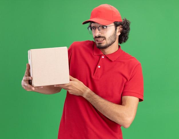 Onder de indruk van jonge bezorger in rood uniform en pet met een bril die een kartonnen doos vasthoudt en kijkt die op een groene muur is geïsoleerd