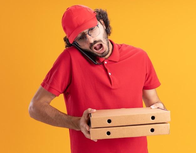 Onder de indruk van jonge bezorger in rood uniform en pet met een bril die pizzapakketten vasthoudt die aan de telefoon praten en naar beneden kijkt geïsoleerd op een oranje muur