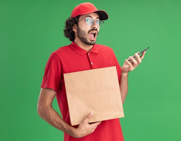 Onder de indruk van jonge blanke bezorger in rood uniform en pet met bril met papieren pakket en mobiele telefoon geïsoleerd op groene muur