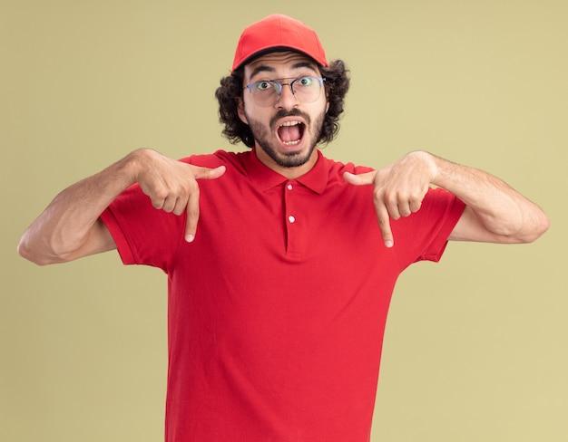 Onder de indruk van jonge blanke bezorger in rood uniform en pet met een bril die naar beneden wijst