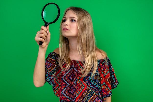 Onder de indruk van jonge blonde vrouw die vergrootglas vasthoudt en bekijkt