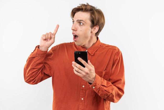 Onder de indruk van jonge knappe kerel met een rood shirt die telefoonpunten vasthoudt op geïsoleerd op een witte muur