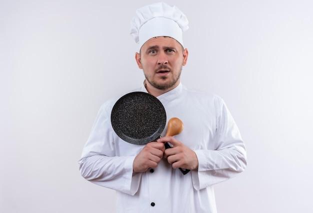 Onder de indruk van jonge knappe kok in chef-kok uniform met lepel en koekenpan op geïsoleerde witte muur