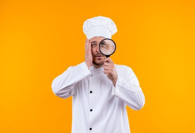 Onder de indruk van jonge knappe kok in uniform van de chef-kok die door vergrootglas kijkt met de hand op het gezicht op geïsoleerde oranje muur met kopieerruimte