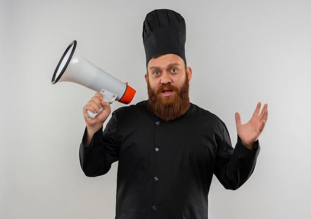 Onder de indruk van jonge knappe kok in uniform van de chef-kok die spreker vasthoudt en hand opsteekt die op een witte muur wordt geïsoleerd