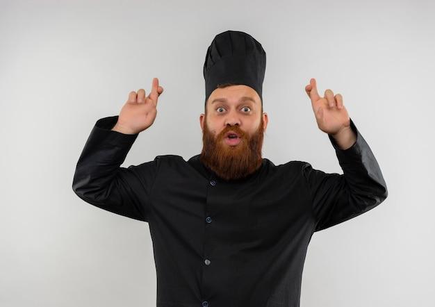 Onder de indruk van jonge knappe kok in uniform van de chef-kok doet gekruiste vingers gebaar geïsoleerd op een witte muur
