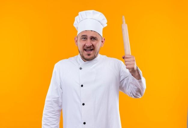 Onder de indruk van jonge knappe kok in uniform van de chef-kok met deegroller geïsoleerd op oranje muur