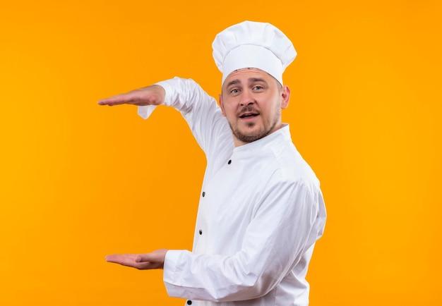 Onder de indruk van jonge knappe kok in uniform van de chef-kok met grootte geïsoleerd op oranje muur