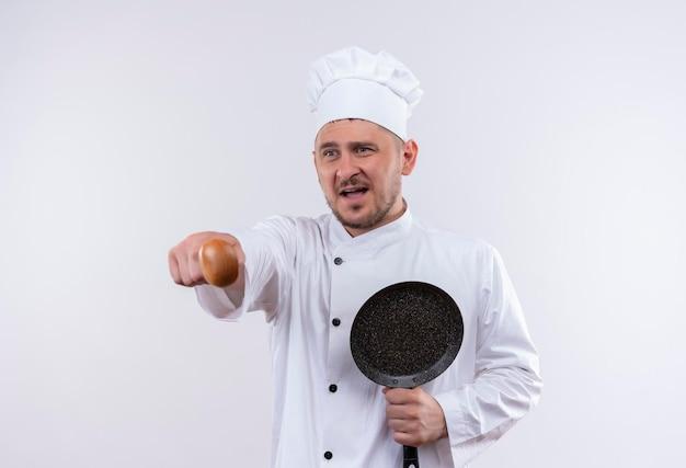 Onder de indruk van jonge knappe kok in uniform van de chef-kok met koekenpan en wijzend met lepel geïsoleerd op een witte muur