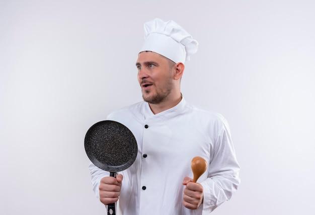 Onder de indruk van jonge knappe kok in uniform van de chef-kok met lepel en koekenpan kijkend naar kant geïsoleerd op een witte muur