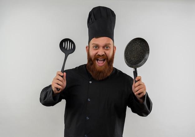 Onder de indruk van jonge knappe kok in uniform van de chef-kok met schuimspaan en koekenpan geïsoleerd op een witte muur