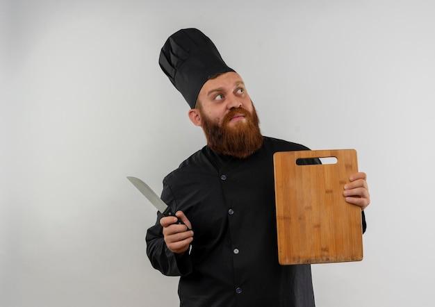 Onder de indruk van jonge knappe kok in uniform van de chef-kok met snijplank en mes kijkend naar kant geïsoleerd op een witte muur met kopieerruimte copy